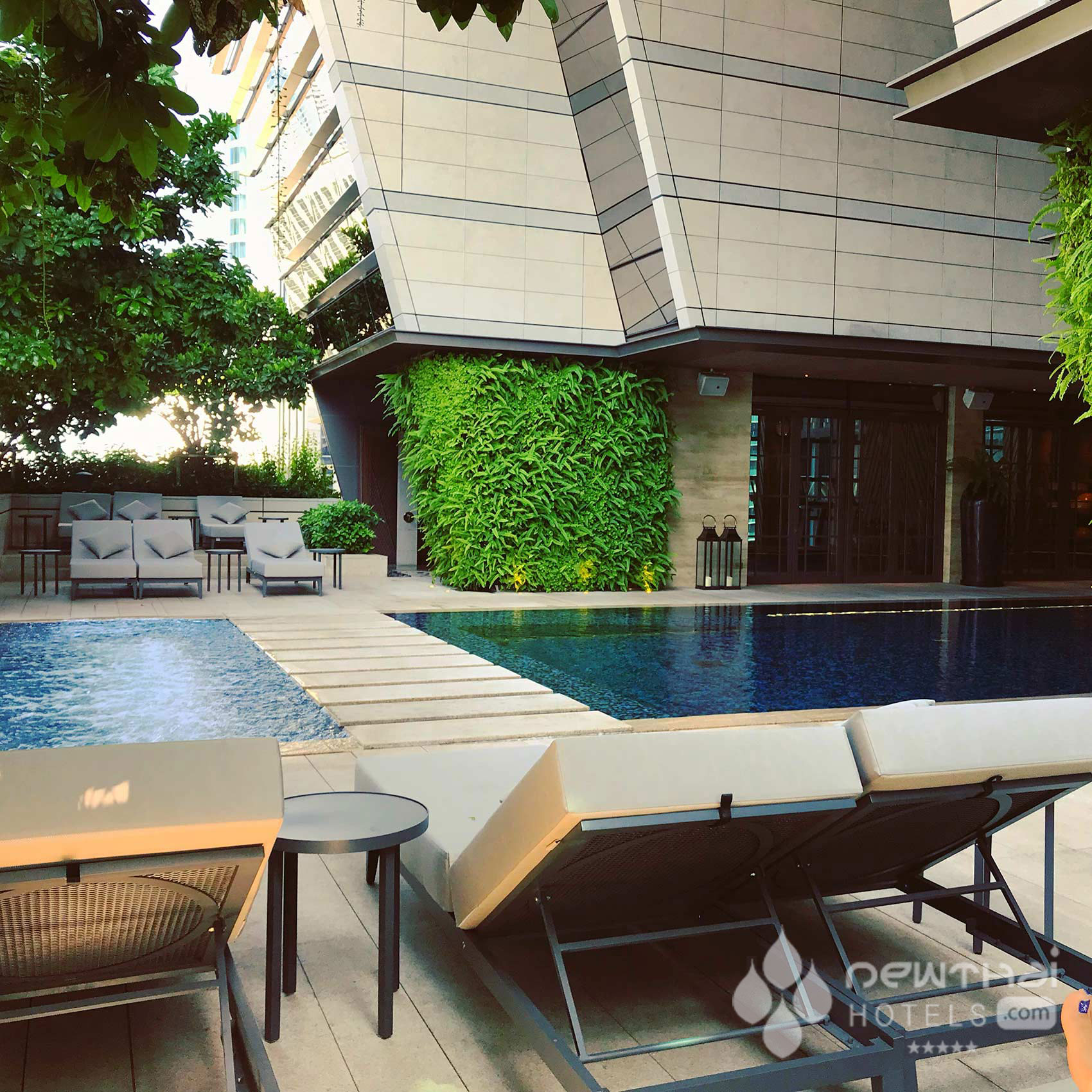 Sun lounges at poolside at Rosewood Bangkok